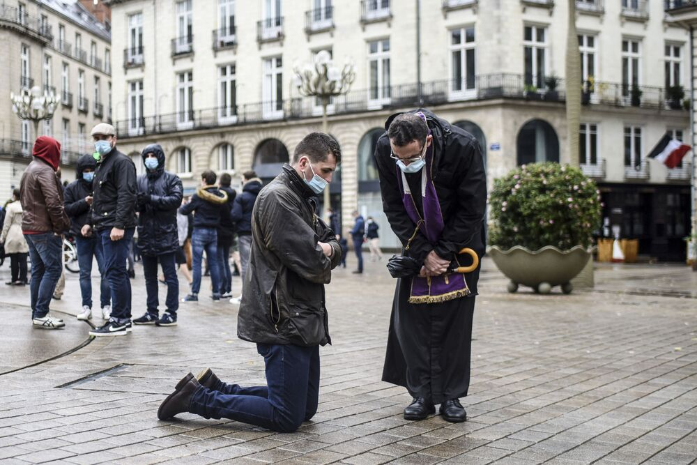 A Catholic priest listens to the confession of a believer during a gathering to call the reopening of places of worship during a national lockdown in France to stop the spread of the novel coronavirus, Covid-19, in Nantes, western France on 15 November 2020.
