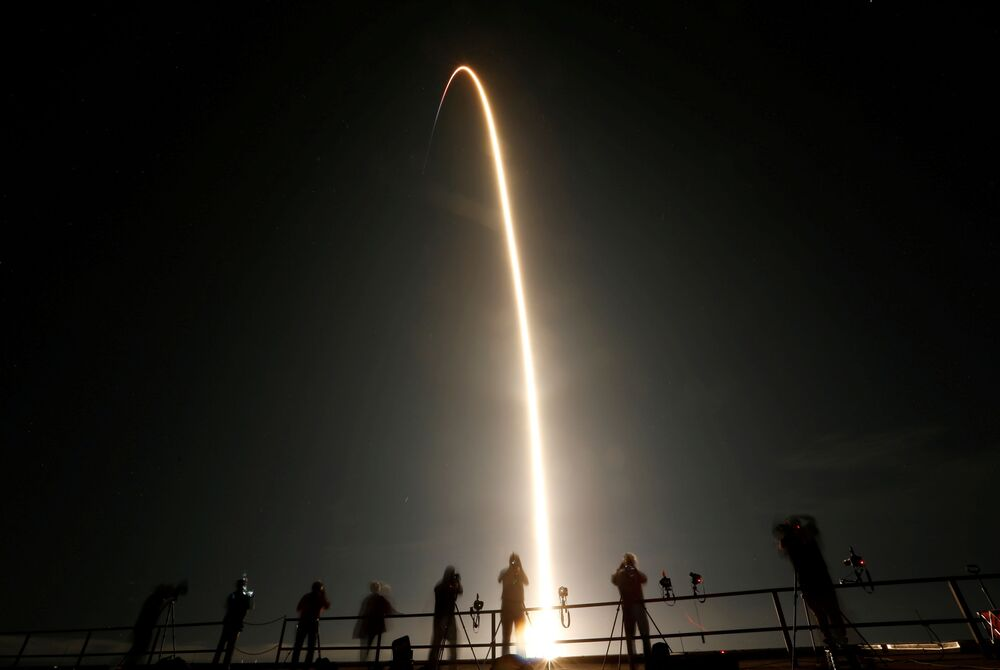 People watch as a SpaceX Falcon 9 rocket, topped with the Crew Dragon capsule, is launched carrying four astronauts on the first operational NASA commercial crew mission at Kennedy Space Center in Cape Canaveral, Florida, US, 15 November 2020.