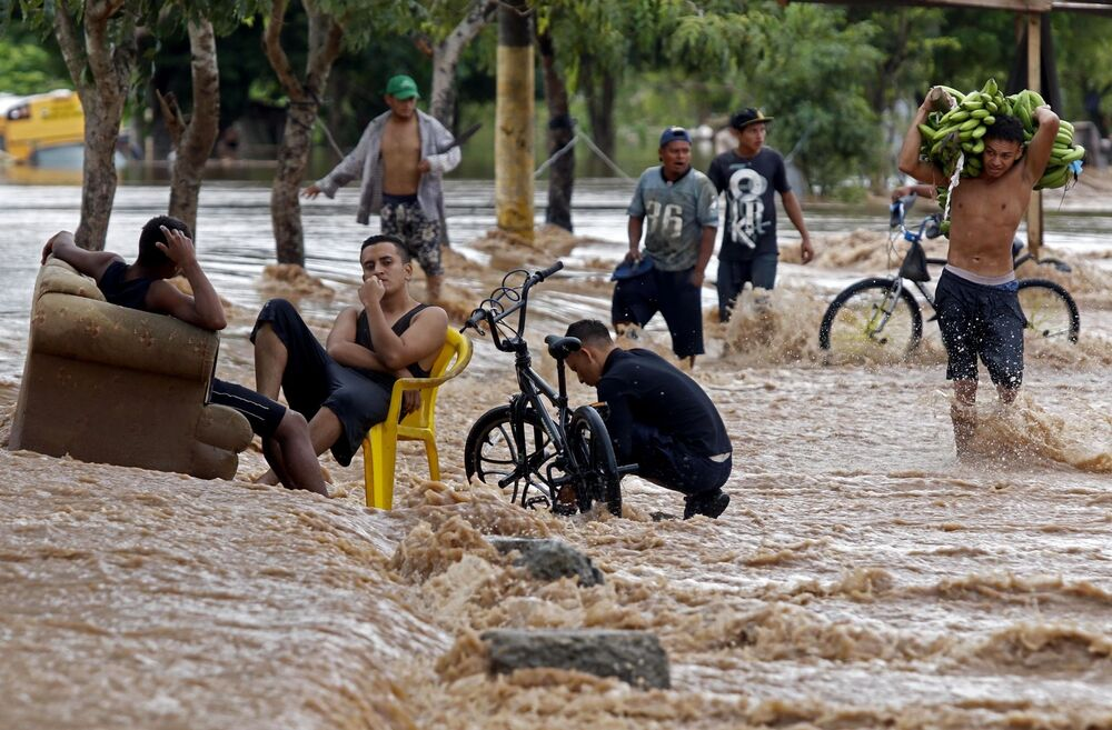 A youngster carries bananas as he wades near men sitting in a flooded street in El Progreso, a department of Yoro, Honduras on 18 November 2020, after the passage of Hurricane Iota, now downgraded to a Tropical Storm. Storm Iota, which made landfall in Nicaragua as a catastrophic Category 5 hurricane Monday, killed at least ten people as it smashed homes, uprooted trees and swamped roads during its destructive advance across Central America.