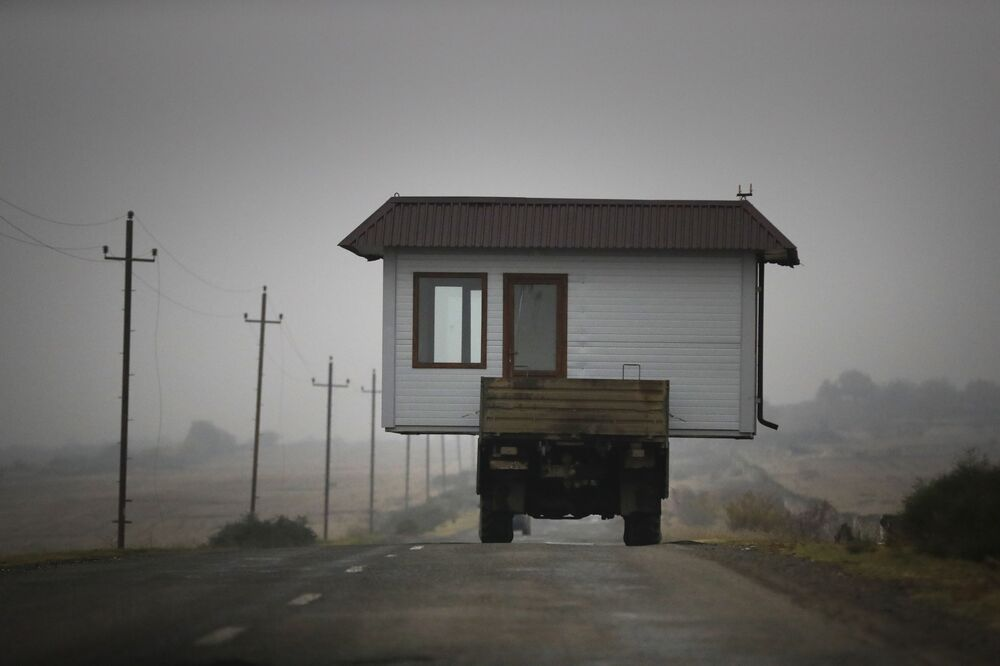 A family drives a truck loaded with a small house along a highway as they leave their home village in the separatist region of Nagorno-Karabakh, Wednesday, 18 November 2020. A Russia-brokered cease-fire to halt six weeks of fighting over Nagorno-Karabakh stipulated that Armenia turn over control of some areas it holds outside the separatist territory's borders to Azerbaijan. Armenians are forced to leave their homes before the region is handed over to control by Azerbaijani forces.