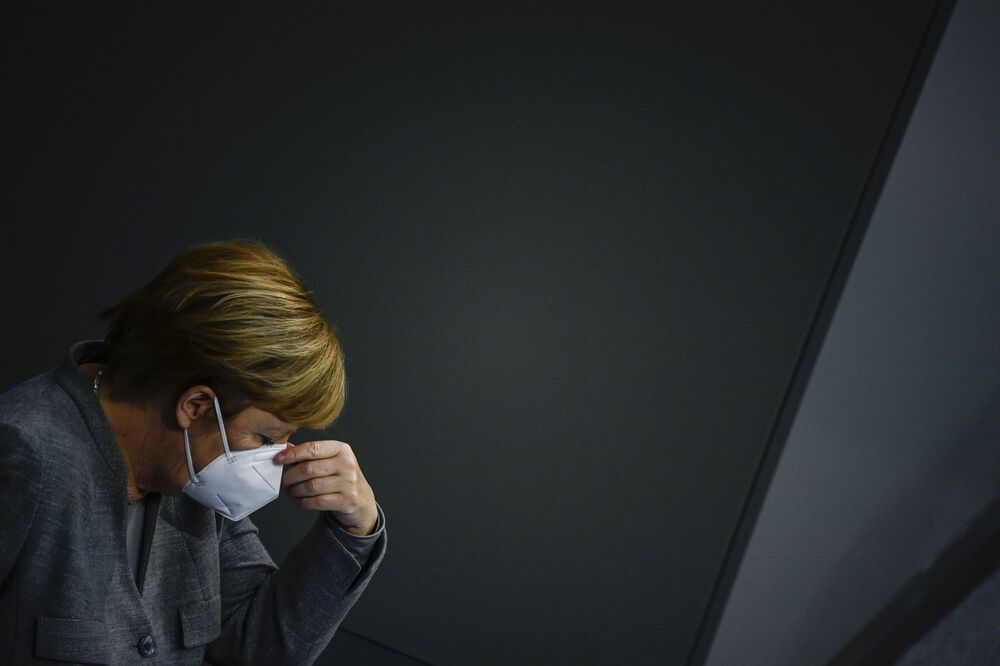 German Chancellor Angela Merkel adjusts her face mask during a session at the Bundestag (lower house of parliament) on 18 November 2020 in Berlin on measures to curb the spread of the novel coronavirus (COVID-19).