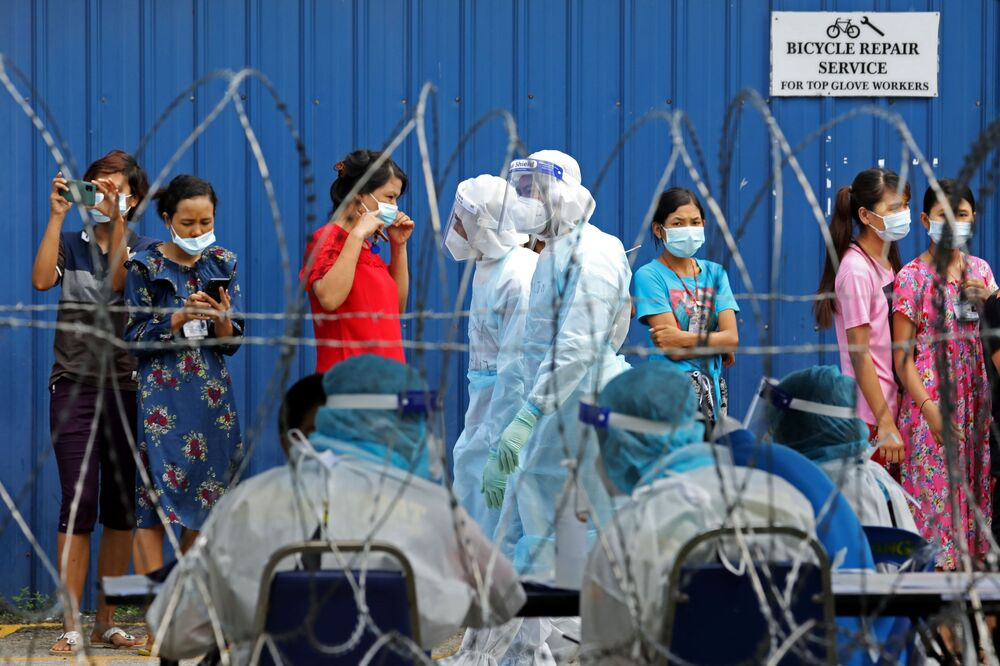 Workers wait in line to be tested for the coronavirus disease (COVID-19) outside a hostel under enhanced lockdown in Klang, Malaysia 18 November 2020.