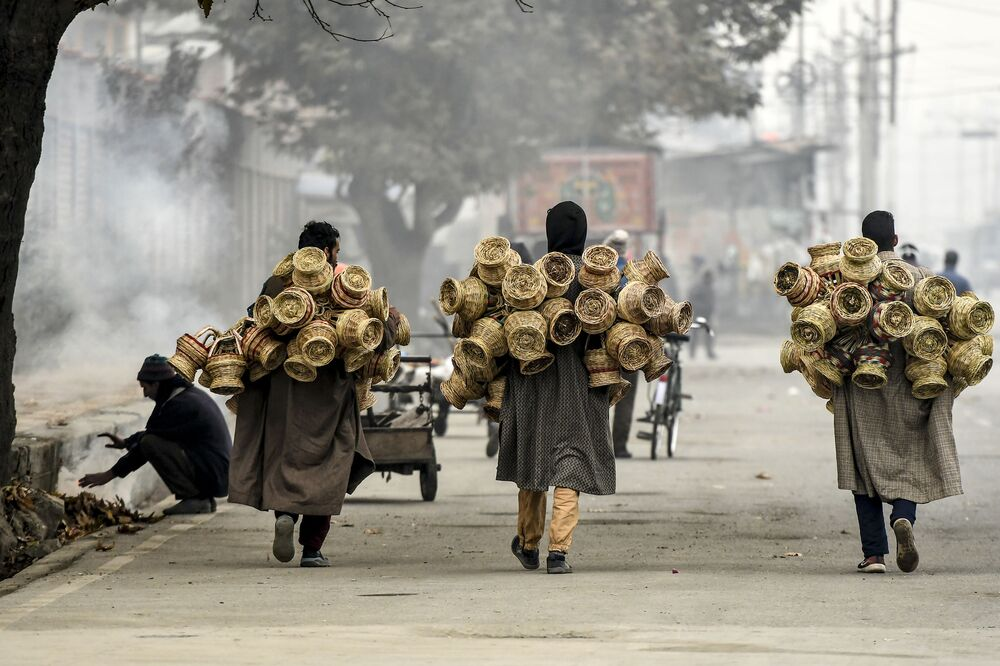 Vendors carry Kangri (earthen pots covered with wicker used to keep people warm) during a foggy day in Srinagar on 19 November 2020.