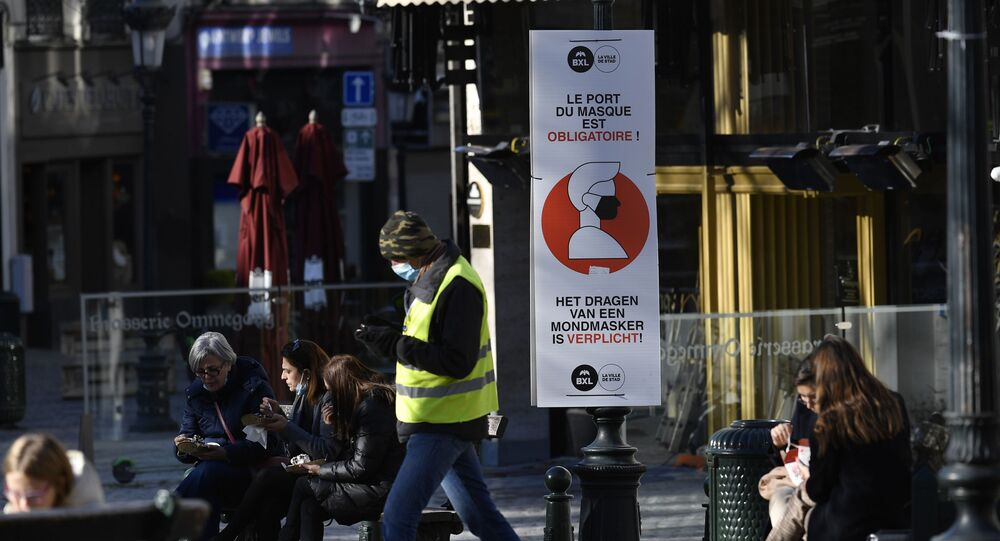 A man wears a face mask as he walks past a sign reading 'wearing a mask is mandatory' on a street in Brussels on November 6, 2020, placed in an attempt to counter the spread of the coronavirus (Covid-19) pandemic.