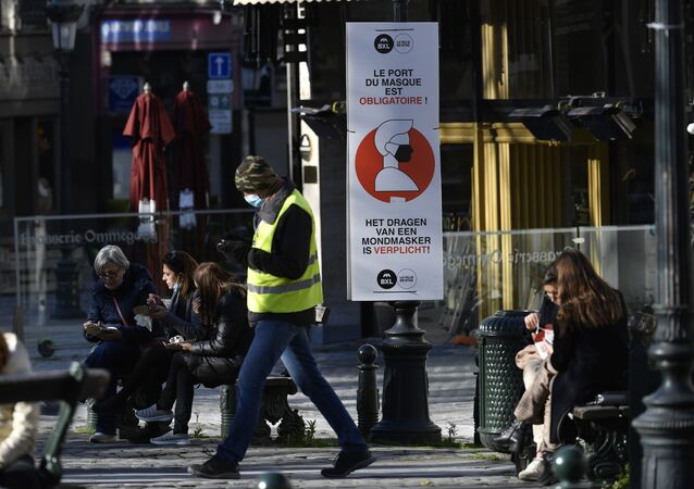 A man wears a face mask as he walks past a sign reading 'wearing a mask is mandatory' on a street in Brussels on 6 November 2020, placed in an attempt to counter the spread of the coronavirus (Covid-19) pandemic.