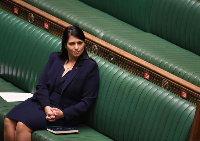 A handout photograph released by the UK Parliament shows Britain's Home Secretary Priti Patel listening as Britain's Prime Minister Boris Johnson speaks in the House of Commons in London on November 2, 2020