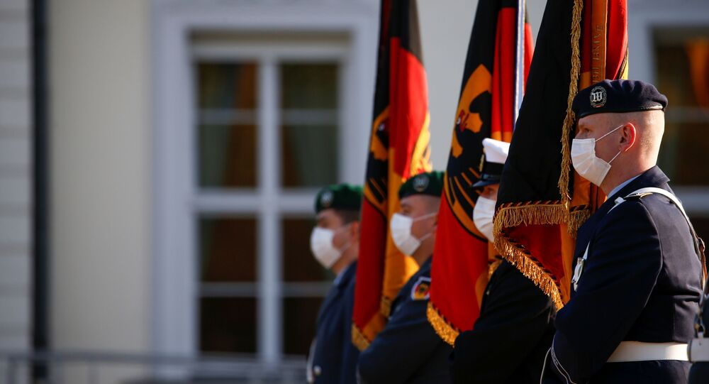 German armed forces Bundeswehr soldiers hold flags outside Bellevue Palace during a swearing-in ceremony, in Berlin, Germany, November 12, 2020.