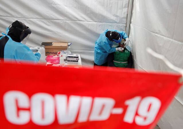 A healthcare worker wearing personal protective equipment (PPE) takes a swab sample from a man to be quick result tested for the coronavirus disease (COVID-19) in Mexico City, Mexico November 20, 2020