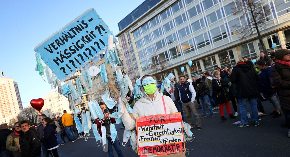 A demonstrator holds a sign with face masks hanging from it during a rally against the government's restrictions following the coronavirus disease (COVID-19) outbreak, in Leipzig, Germany, 7 November 2020.