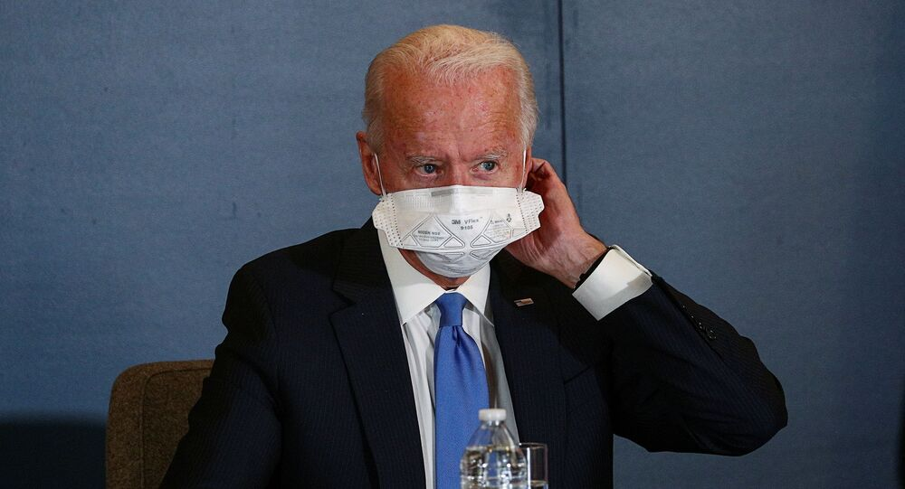 Joe Biden removes his face mask as he meets with Speaker of the House Nancy Pelosi (D-CA) and Senate Minority Leader Chuck Schumer (D-NY) at his transition headquarters in the Queen theater in Wilmington, Delaware, US, 20 November 2020.