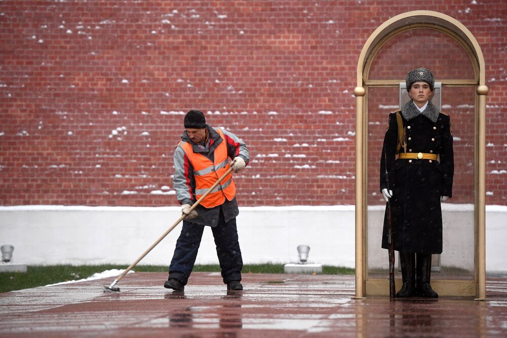 A janitor cleans the snow near the Tomb of the Unknown Soldier by the Kremlin wall