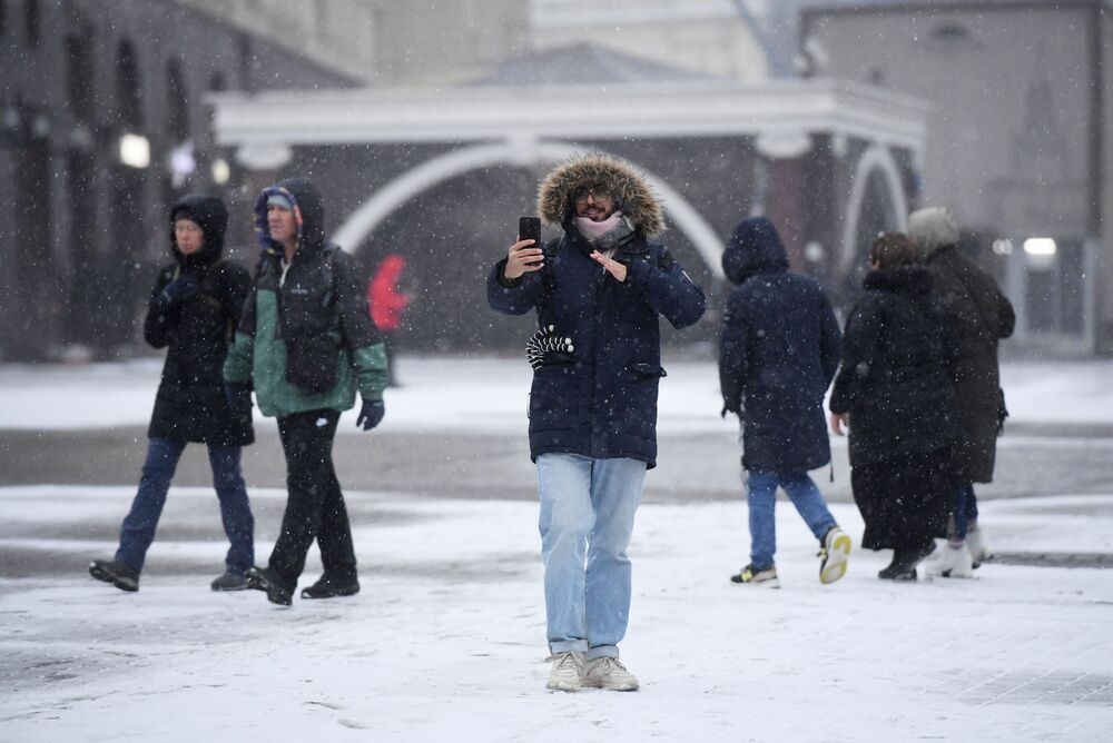 A man takes a selfie with a snowy Moscow street in the background
