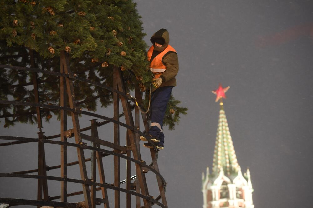 A worker installs an artificial Christmas tree in Red Square