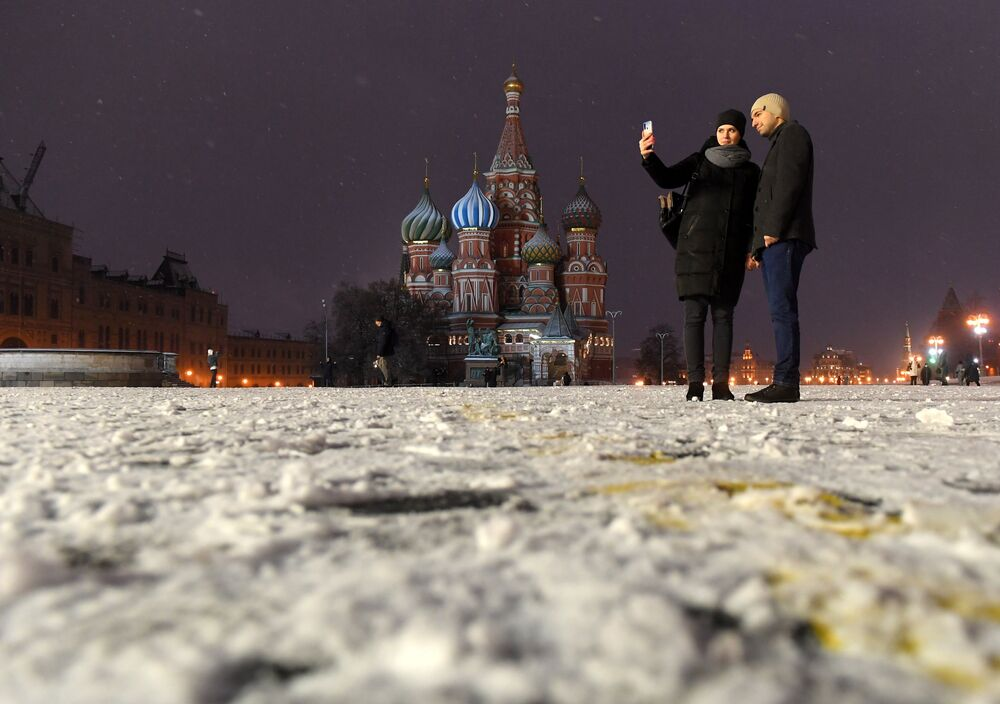 A pair takes a selfie in Red Square with Saint Basil's Cathedral in the background
