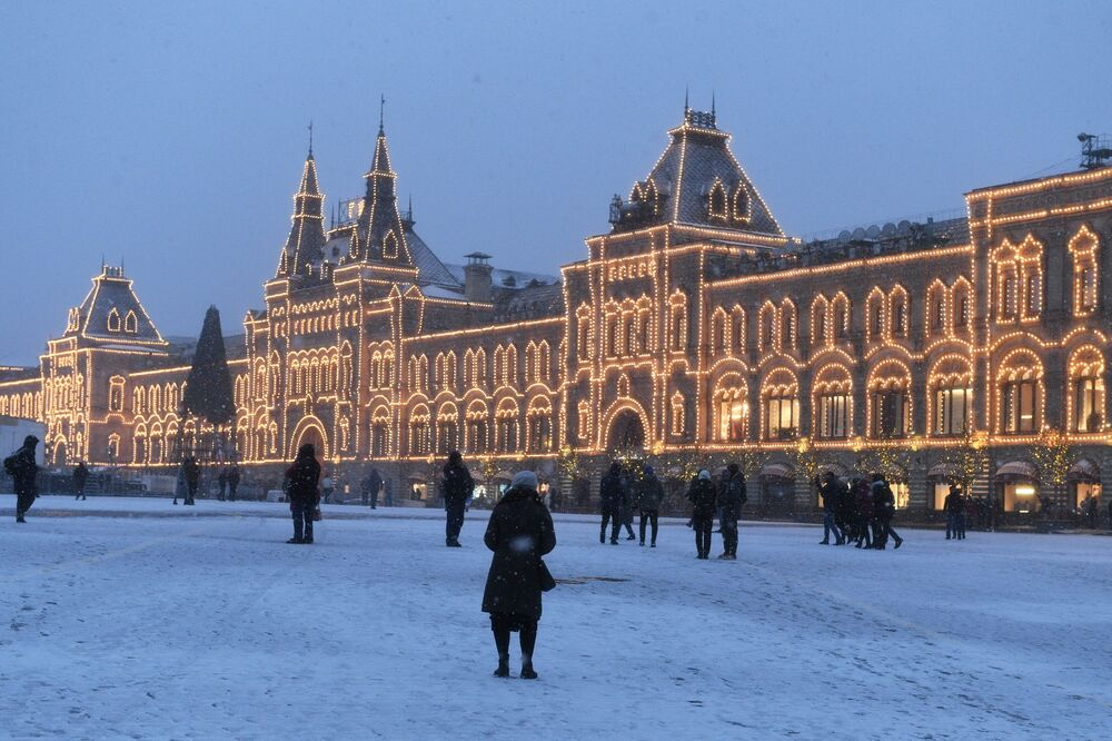 People enjoy snowy weather near the GUM shopping centre in Red Square