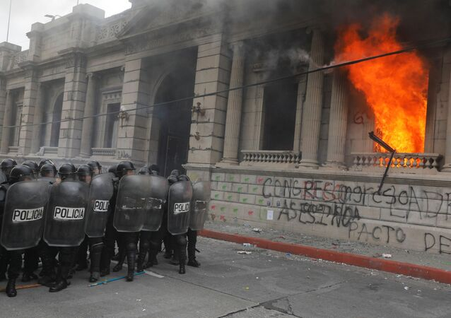 Riot police stand in formation as demonstrators set an office of the Congress building on fire during a protest demanding the resignation of President Alejandro Giammattei, in Guatemala City, Guatemala November 21, 2020.