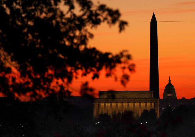 The sky turns shades of red as the sun rises behind the U.S. Capitol, the Washington Monument and the Lincoln Memorial in Washington, U.S., November 19, 2020.