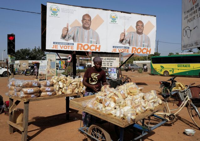 A woman displays bread  for sale near a campaign banner of presidential candidate Roch Kabore in Ouagadougou, Burkina Faso November 20, 2020.