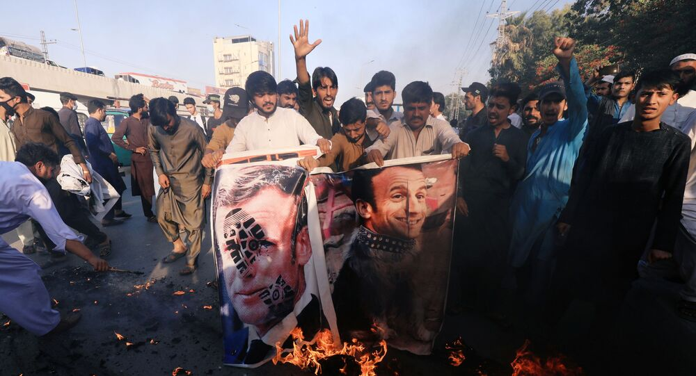 People chant slogans as they set fire to a banner with an image of French President Emmanuel Macron during a protest against cartoon publications of Prophet Mohammad in France and French President Emmanuel Macron's comments, in Peshawar, Pakistan 27 October 2020.