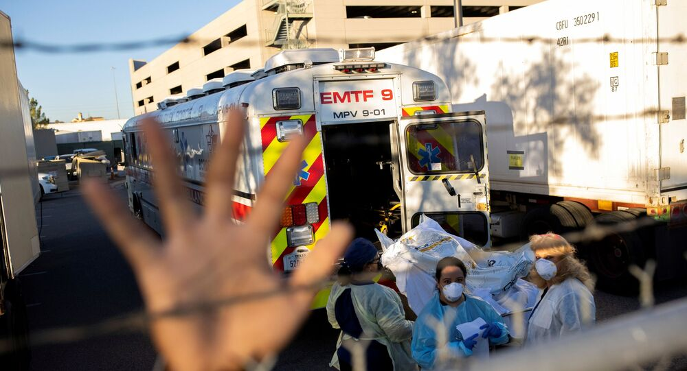 An El Paso County Sheriff's Officer tries to block photographs from being taken as bodies are moved to refrigerated trailers, deployed during a surge of coronavirus disease (COVID-19) deaths, outside the County of El Paso Medical Examiners Office in El Paso, Texas, 16 November 2020