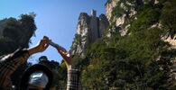 A tourist with a face mask takes a picture with her mobile phone at the entrance of the Bailong Elevator in the Zhangjiajie National Forest Park in China's Hunan province.