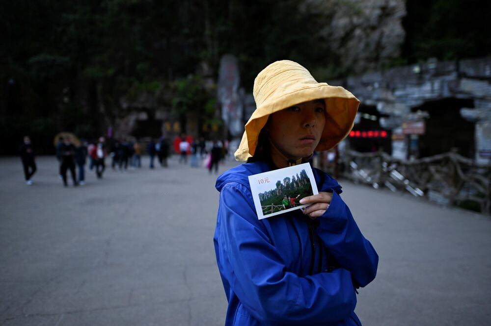 A vendor waits for tourists to take travel photos at the entrance of the Bailong Elevator in Zhangjiajie National Forest Park, China's Hunan province.