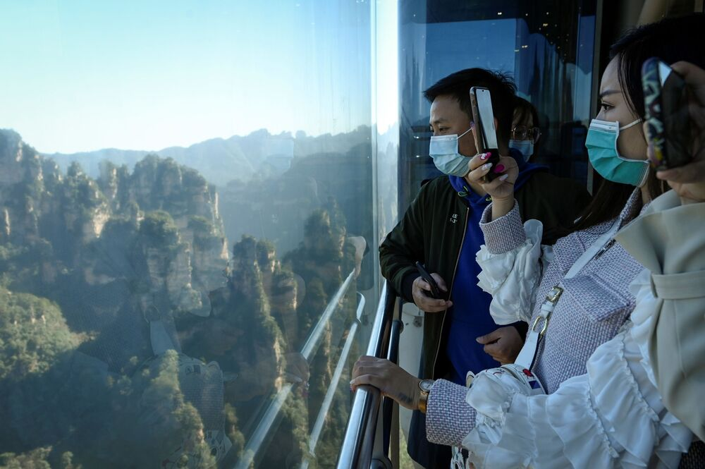 Tourists take pictures of the scenery as they ride the Bailong Elevator in  Zhangjiajie National Forest Park, China's Hunan province.