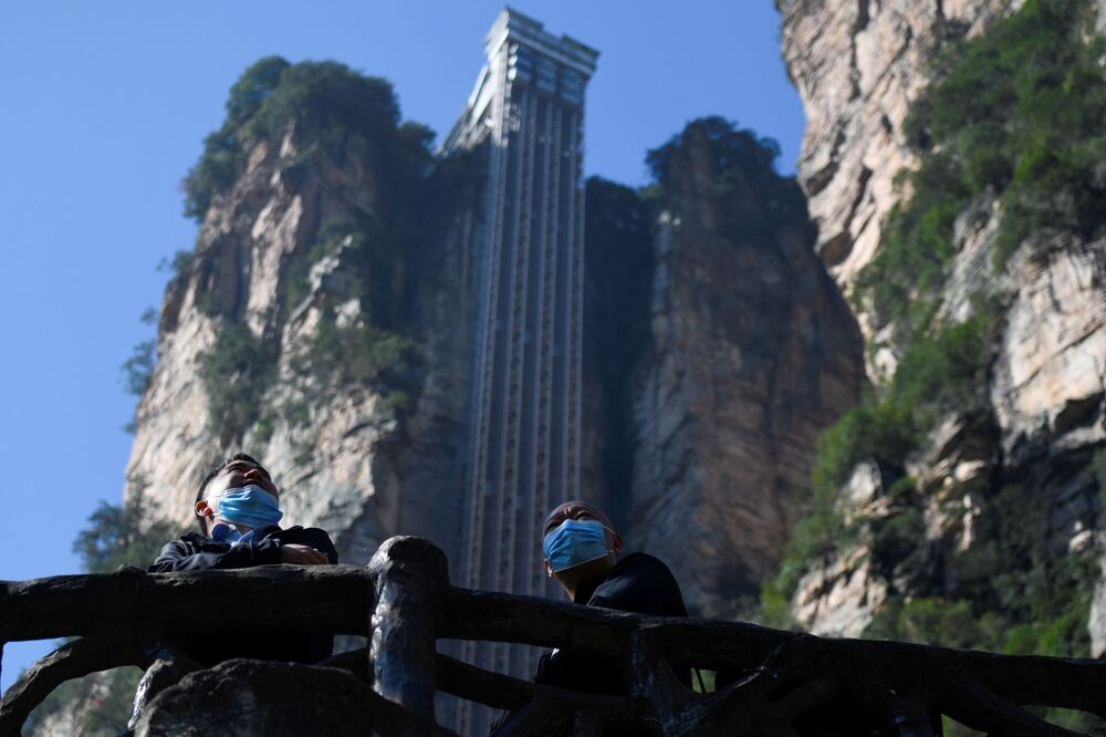 Two tourists wearing face masks look out in front of the Bailong Elevator in Zhangjiajie National Forest Park, China's Hunan province.