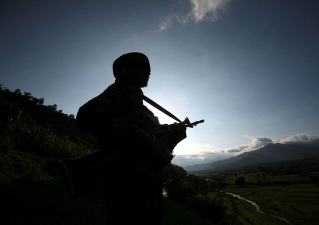 An Indian army soldier stands guard while patrolling near the Line of Control, a ceasefire line dividing Kashmir between India and Pakistan, in Poonch district August 7, 2013.