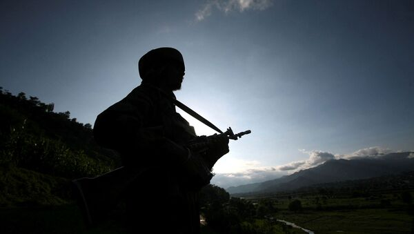 An Indian army soldier stands guard while patrolling near the Line of Control, a ceasefire line dividing Kashmir between India and Pakistan, in Poonch district August 7, 2013.  - Sputnik International