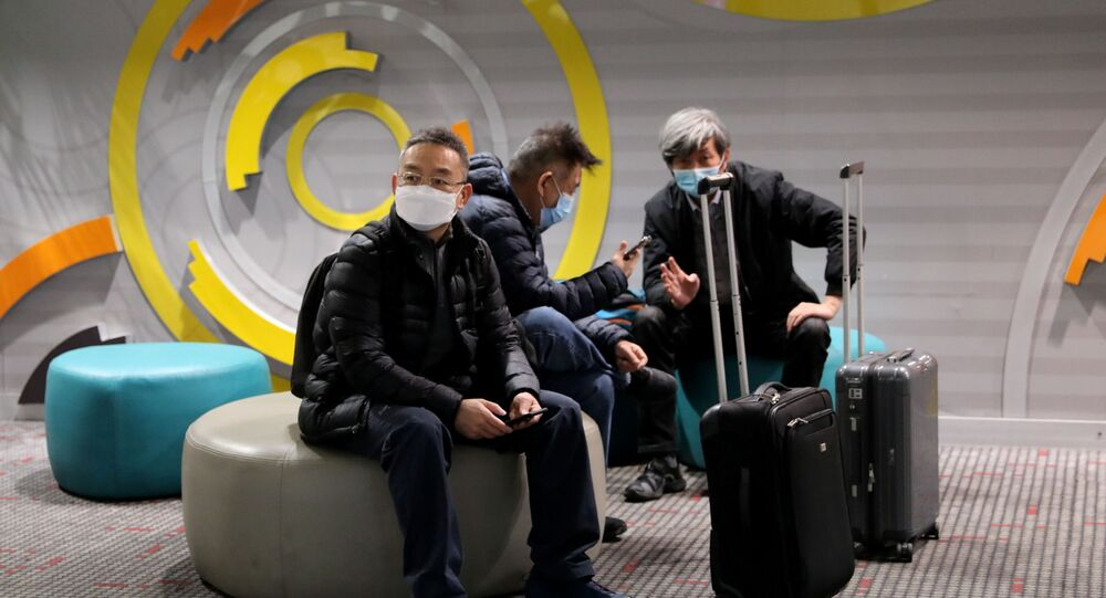 Travellers wearing face masks sit at Beijing Capital International Airport, following the global outbreak of the coronavirus disease (COVID-19), in Beijing, China November 22, 2020.