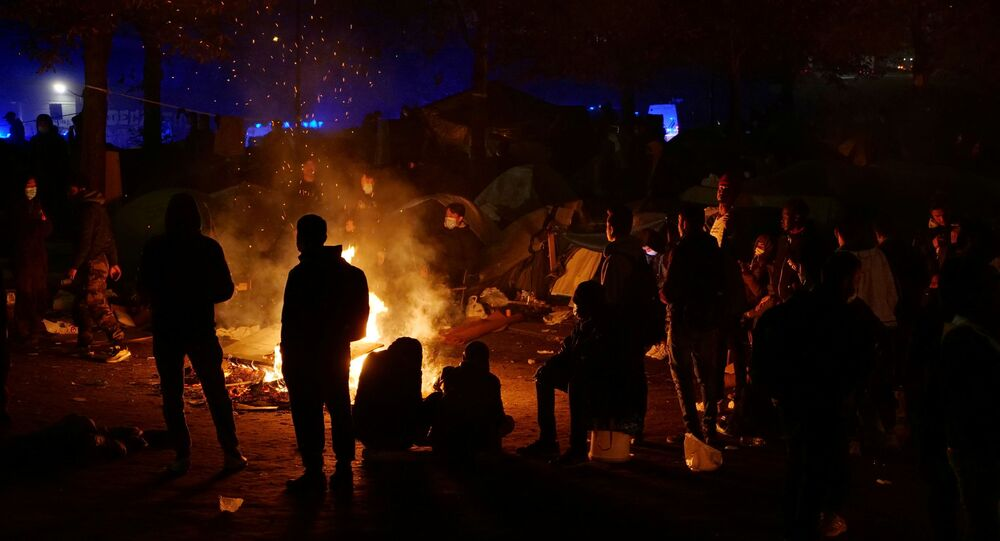 Migrants are seen in silhouette as they gather near a fire before being evacuated by French gendarmes at a makeshift migrant camp near the A1 highway in Saint-Denis near Paris, France, November 17, 2020.