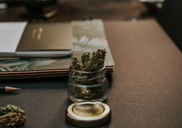 Close-Up Photo of Kush On Glass Container