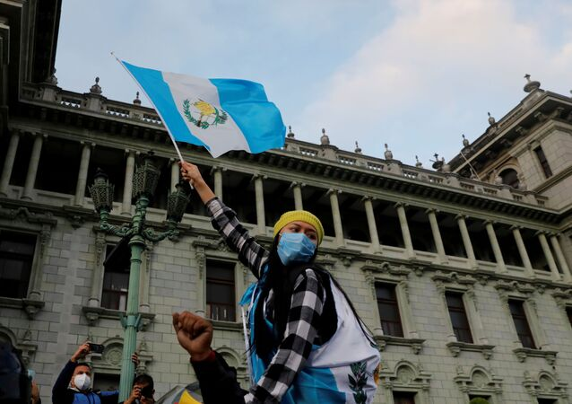 A woman holds up a Guatemalan flag, during a protest to demand the resignation of President Alejandro Giammattei, a day after demonstrators set fire to a part of the Congress building in Guatemala City, Guatemala November 22, 2020.