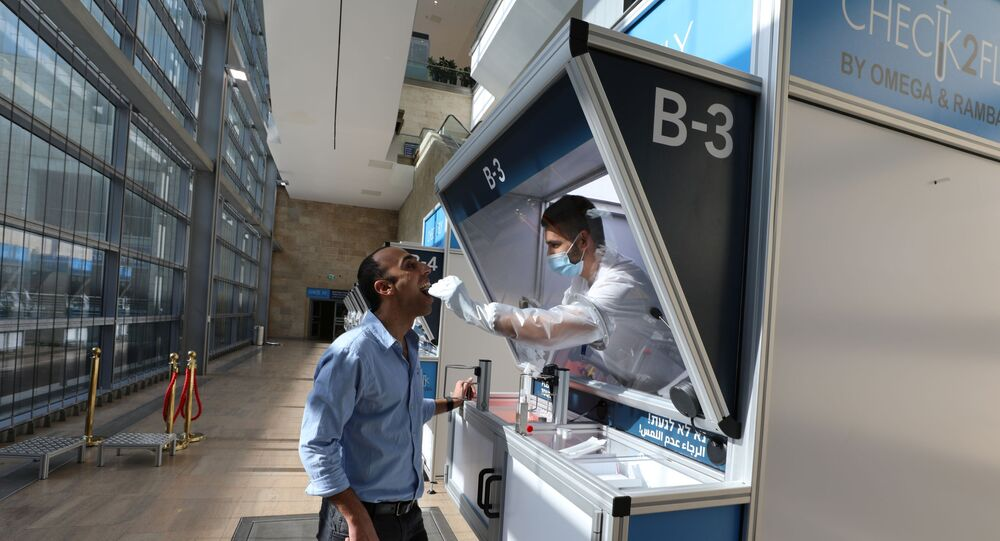 People demonstrate operating of the coronavirus disease (COVID-19) checking system, at Ben Gurion International airport in Lod, Israel November 9, 2020.