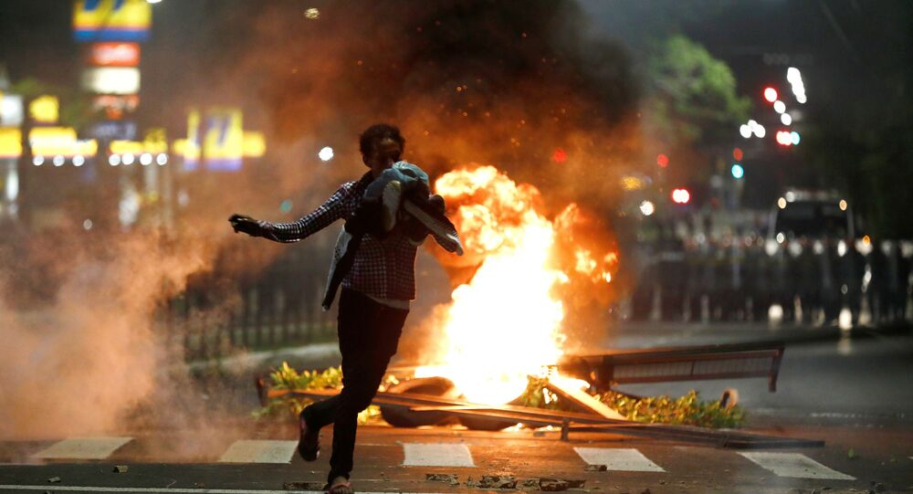 A demonstrator runs during a protest against racism, after Joao Alberto Silveira Freitas was beaten to death by security guards at a Carrefour supermarket in Porto Alegre, Brazil, November 23, 2020