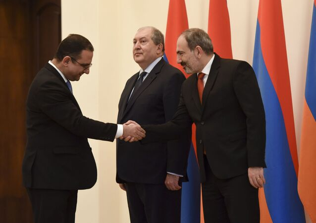 Armenian Economic Development and Investments Minister Tigran Khachatryan shakes hands with Prime Minister Nikol Pashinyan as President Armen Sarkissian looks on during the inauguration ceremony for the new government members in Yerevan, Armenia