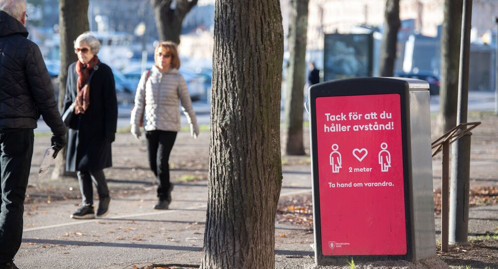 People strollIing in the cold but sunny weather pass a sign asking to maintain social distancing, amid the continuous spread of the coronavirus disease (COVID-19) pandemic, in Stockholm, Sweden, November 20, 2020