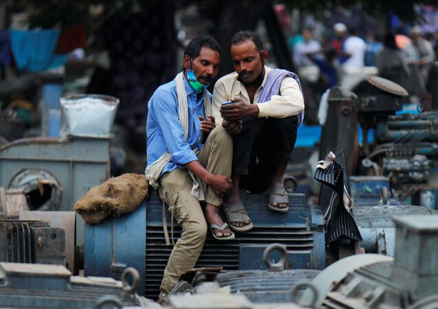 Men wearing protective face masks on their chins, amid the coronavirus disease (COVID-19) outbreak, watch a video on a mobile phone as they sit at a second-hand motor parts market in the old quarters of Delhi, India, November 16, 2020