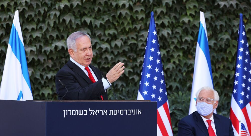 "Israeli Prime Minister Benjamin Netanyahu gestures during a special ceremony with the U.S. Ambassador to Israel David Friedman to sign an extension of the Israel-U.S. scientific cooperation agreement in ""Judea, Samaria"" (the biblical names for the West Bank) and the Golan Heights, at Ariel University in the Jewish settlement of Ariel, in the Israeli-occupied West Bank October 28, 2020. Emil Salman/Pool via REUTERS"