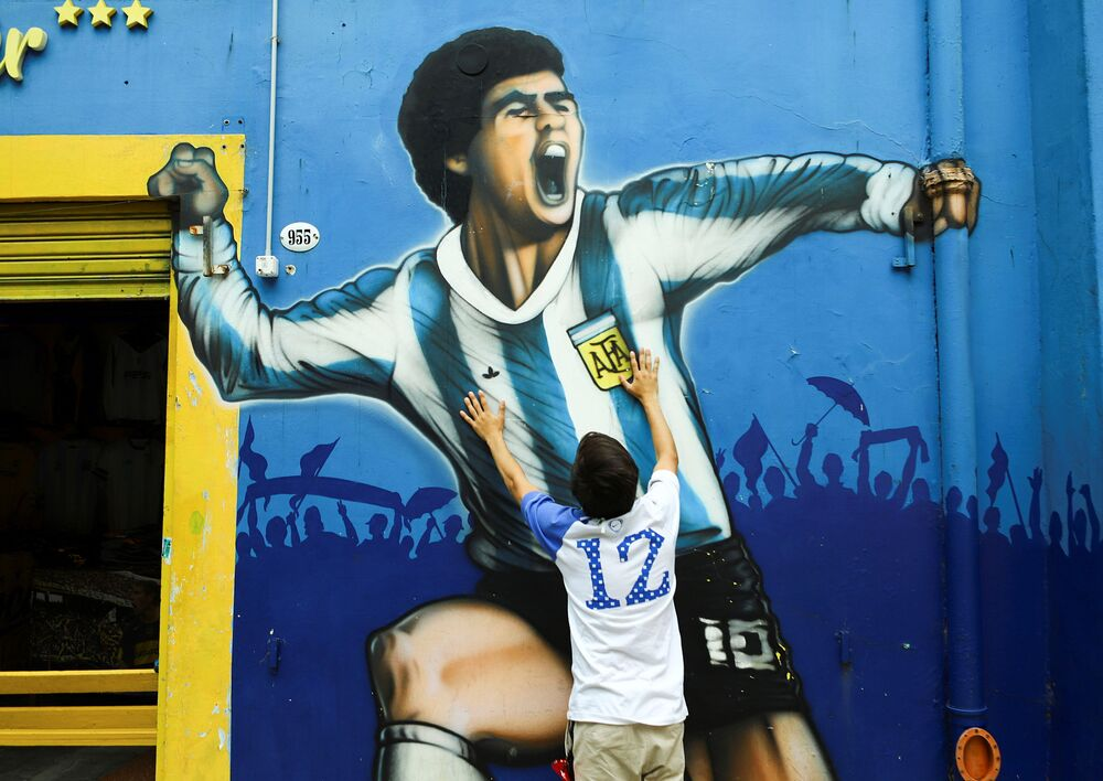 A fan mourns the death of soccer legend Diego Maradona, outside the Alberto J. Armando La Bombonera Stadium, in Buenos Aires, Argentina 25 November 2020.