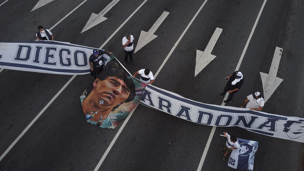 Soccer fans carry a banner of Diego Maradona in downtown Buenos Aires, Argentina, Wednesday, 25 Nov 2020. Diego Maradona, the Argentine soccer great who was among the best players ever and who led his country to the 1986 World Cup title, died from a heart attack at his home in Buenos Aires. He was 60.
