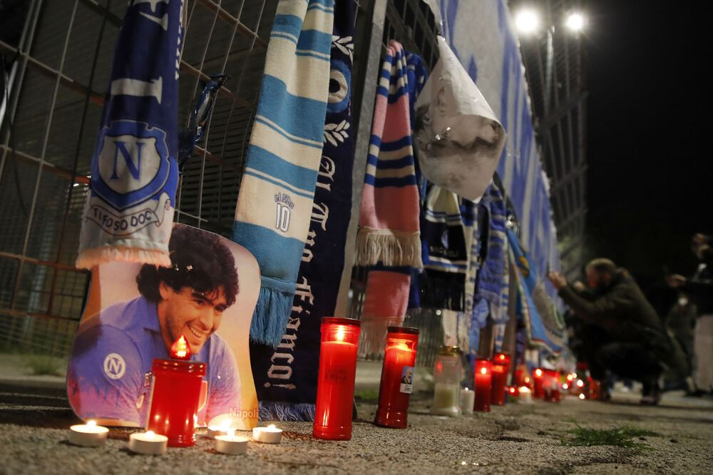 Candles lie next to a picture of Diego Armando Maradona outside the San Paolo Stadium to pay their homage to the late soccer legend, in Naples, Italy, Wednesday, 25 Nov. 2020.