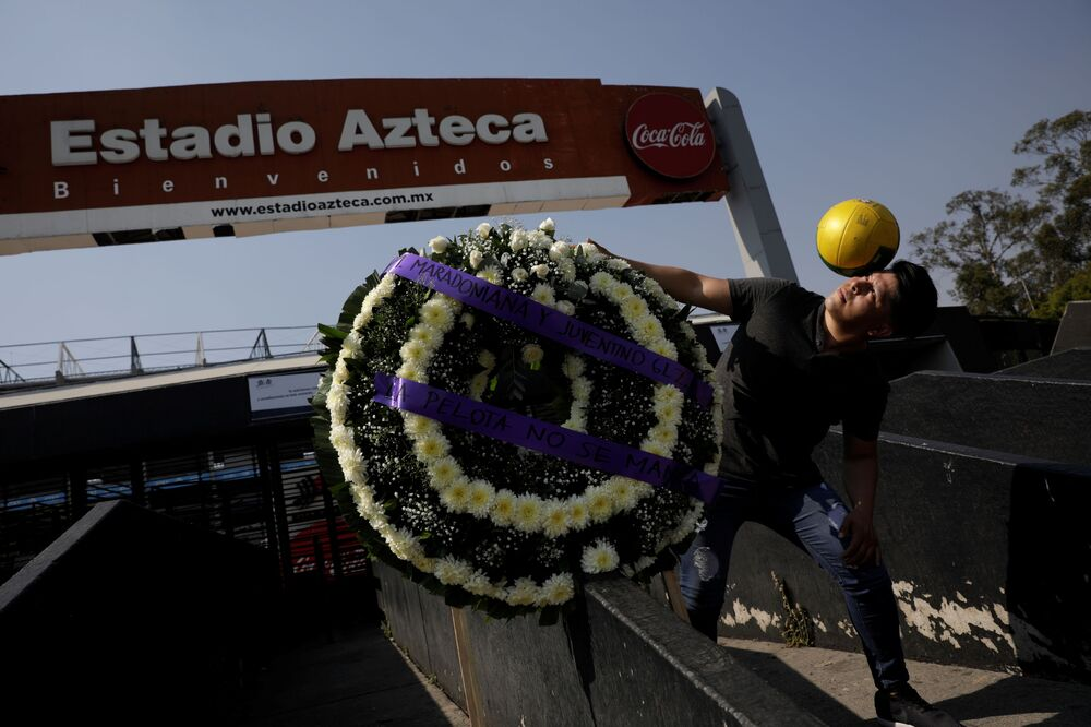 A fan controls a ball while posing for a photo next to a wreath in memory of late Argentinian soccer legend Diego Armando Maradona outside the Azteca Stadium, in Mexico City, Mexico November 25, 2020.