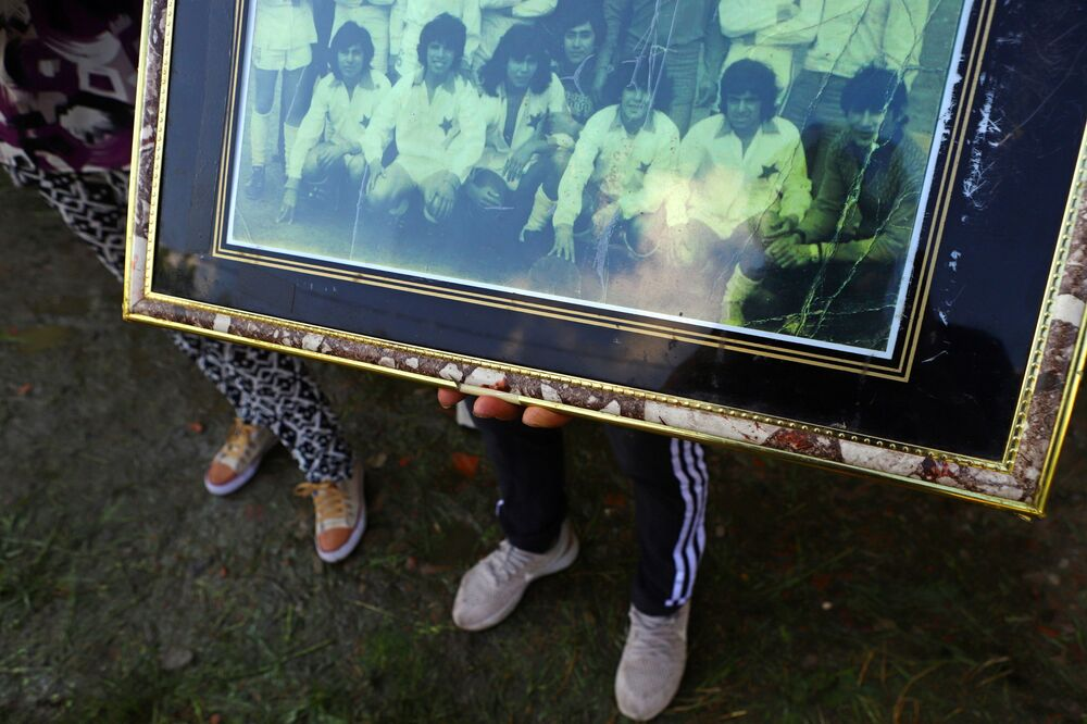 A woman holds a picture of soccer legend Diego Maradona (3rd L) as a teenager and his teammates from Estrella Roja, in the low income neighbourhood Villa Fiorito where Maradona spent his childhood, on the outskirts of Buenos Aires, Argentina 25 November 2020.