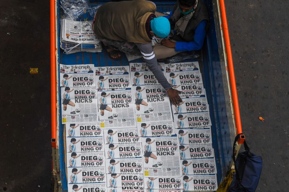 Hawkers sell newspapers featuring front-page news of the death of Argentina's player Diego Maradona in Kolkata on 26 November 2020.