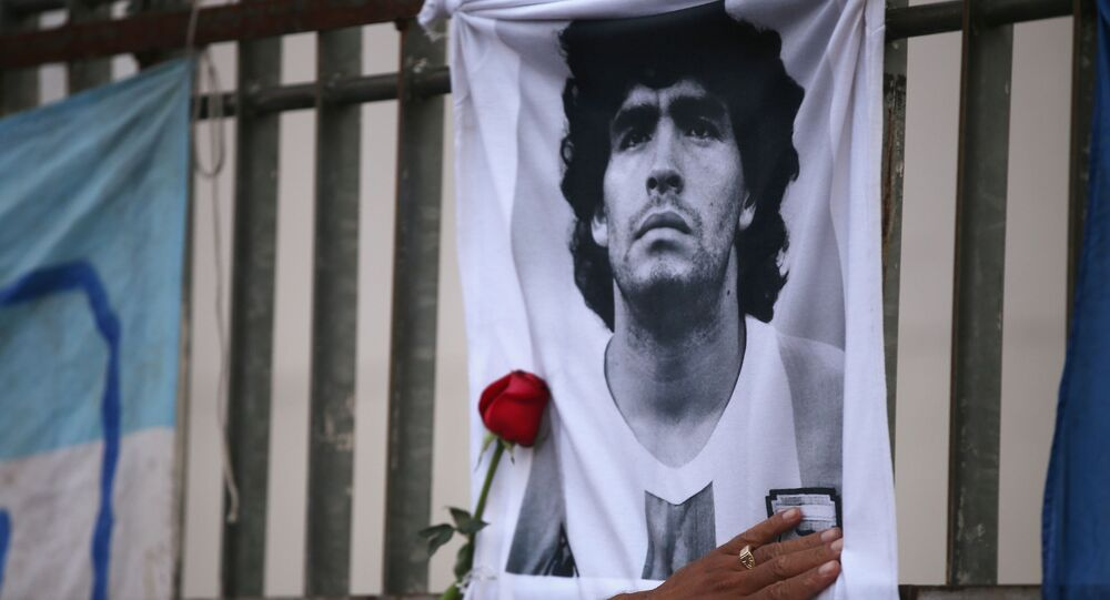 A rose is placed next to a banner of Argentine soccer great Diego Maradona as fans gather to mourn his death, at the Obelisk of Buenos Aires, Argentina November 25, 2020
