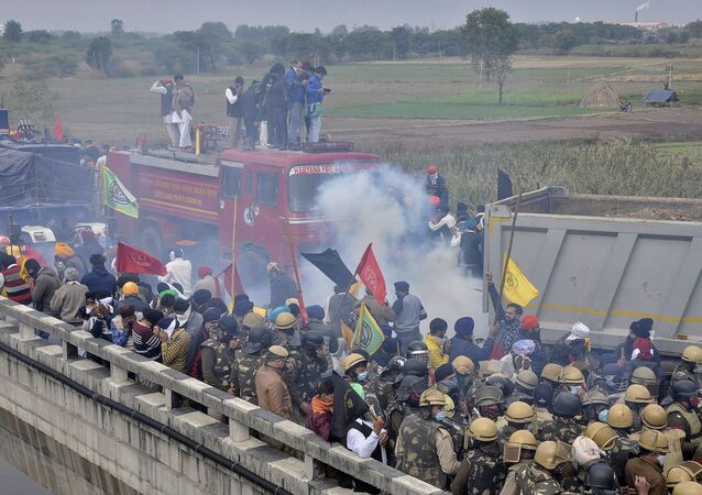Farmers run away as police fire tear smoke shells to disperse the protesting farmers as they try to march to Delhi to protest against farm bills passed by India's parliament, near Ambala, India, November 26, 2020