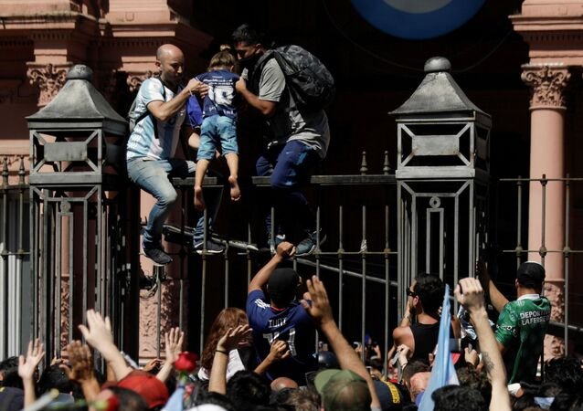 Men help a child to climb on the fence of the Casa Rosada presidential palace as people gather to mourn the death of soccer legend Diego Armando Maradona, in Buenos Aires, Argentina November 26, 2020.