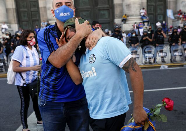 People mourn the death of soccer legend Diego Armando Maradona, in front of the Casa Rosada presidential palace in Buenos Aires, Argentina, November 26, 2020.